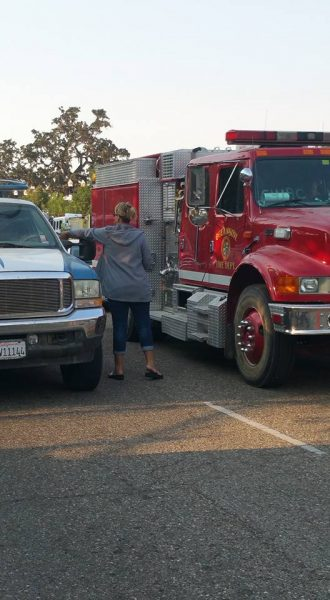 A Girl Scout parent is seen tossing boxes of cookies to passing firefighters. Photo contributed by Jeanne Gard